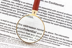 Confidentiality. Closeup of magnifying glass on security related text on letter with sensitive business documents in background. For privacy and confidentiality Royalty Free Stock Photos