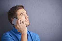 Confidnet man with handy. Close-up shot of a handsome young man making call with his cellphone while sitting in front of a grey wall Royalty Free Stock Photo