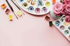 Configuração criativa do plano de paletas da aquarela, escovas de pintura, ramalhete de rosas cor-de-rosa Local de trabalho do ar Foto de Stock