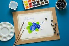 Configuração criativa do plano do local de trabalho do artista Vista superior na tabela com os mirtilos pintados na placa, copo d Imagens de Stock Royalty Free