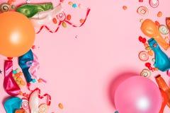 Configuração do plano da celebração Doces com artigos coloridos do partido em vagabundos cor-de-rosa Imagens de Stock