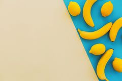 Configuração do plano do verão bananas amarelas com os limões no papel azul na moda fotos de stock royalty free