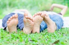 Configuração do rapaz pequeno nos pés da mostra da grama imagens de stock