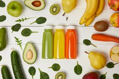 configuração lisa com as garrafas com os batidos da desintoxicação na fileira com frutas e legumes no fundo de madeira Imagem de Stock