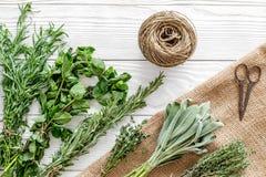 A configuração lisa com ervas e hortaliças frescas para secar e fazer especiarias ajustou-se no fundo de madeira branco da cozinh imagem de stock