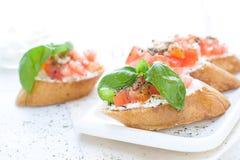 Configuração lisa com os bruschettas com queijo creme, tomates e manjericão Fotos de Stock Royalty Free
