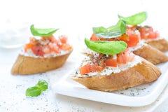 Configuração lisa com os bruschettas com queijo creme, tomates e manjericão Imagens de Stock