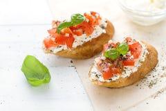 Configuração lisa com os bruschettas com queijo creme, tomates e manjericão Fotografia de Stock Royalty Free