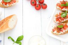 Configuração lisa com os bruschettas com queijo creme, tomates e manjericão Vista superior Imagens de Stock