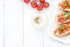 Configuração lisa com os bruschettas com queijo creme, tomates e manjericão Vista superior Fotos de Stock Royalty Free