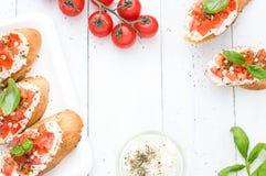 Configuração lisa com os bruschettas com queijo creme, tomates e manjericão Vista superior Foto de Stock Royalty Free