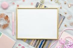 Configuração lisa com quadro dourado, e materiais de escritório no fundo branco Modelo do rosa da vista superior fotografia de stock royalty free