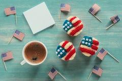 Configuração lisa com queques arranjados, xícara de café e as bandeiras americanas no tabletop de madeira Imagem de Stock