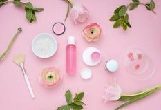Configuração lisa cor-de-rosa cosmética natural com flores Vista superior Foto de Stock