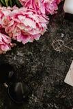 Configuração lisa da beleza com acessórios, perfume, cosméticos e peônias em um fundo de mármore escuro imagem de stock