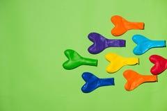 Configuração lisa da celebração com os balões coloridos no fundo verde Foto de Stock