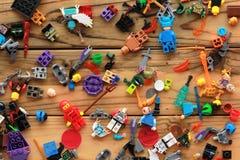 A configuração lisa de brinquedos de Lego dispersou na tabela de madeira Imagens de Stock