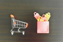 Configuração lisa de Mini Shopping Cart e de Mini Shopping Bags na tabela de madeira fotos de stock royalty free