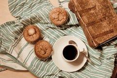 Configuração lisa de um petisco com queques, café e um bom livro imagens de stock royalty free