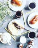 Configuração lisa do café da manhã com flores, café, bule, leite, propagação do chocolate e os bolos doces Fotografia de Stock