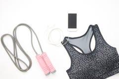 Configuração lisa do smartphone, do sutiã do esporte e dos equipamentos de esporte no branco imagem de stock