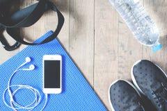 Configuração lisa do telefone celular com fones de ouvido e equipamentos de esporte no fundo de madeira Fotografia de Stock Royalty Free