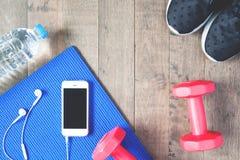 Configuração lisa do telefone celular com fones de ouvido e equipamentos de esporte no fundo de madeira Fotos de Stock Royalty Free