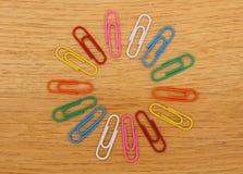 Configuração lisa dos clipes coloridos no círculo pequeno do fundo de madeira fotos de stock