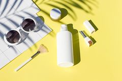 Configuração lisa dos cosméticos amarelos do verão com óculos de sol Beleza da vista superior Fotografia de Stock Royalty Free