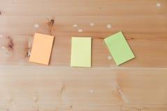 Configuração lisa dos materiais de escritório - notas pegajosas coloridas na BO de madeira Imagens de Stock Royalty Free