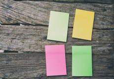 Configuração lisa dos materiais de escritório - notas pegajosas coloridas na BO de madeira Imagens de Stock