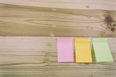 Configuração lisa dos materiais de escritório - notas pegajosas coloridas na BO de madeira Imagem de Stock Royalty Free