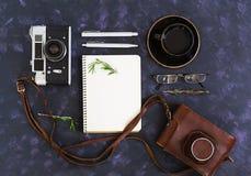 Configuração lisa, mesa da tabela do escritório da vista superior Espaço de trabalho da mesa com câmera retro, diário, pena, vidr Foto de Stock