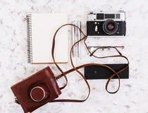 Configuração lisa, mesa da tabela do escritório da vista superior Espaço de trabalho da mesa com câmera retro, diário, pena, vidr Fotos de Stock