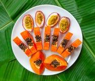Configuração lisa Nutrição do vegetariano as partes da papaia e o fruto de paixão na placa branca com banana verde saem do fundo, fotos de stock royalty free