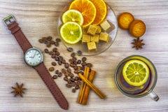 Configuração lisa Relógios do ` s dos homens com correia de couro Fatias de limão e de laranja em uns pires Copo do chá com limão fotos de stock