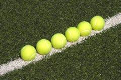 Configurações amarelas das esferas de tênis na corte de grama Imagem de Stock Royalty Free