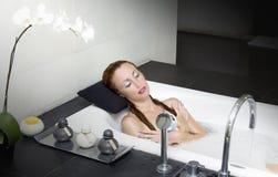 Configurações da menina nos soapsuds no banho foto de stock royalty free