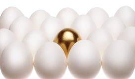 Configurações de um ovo do ouro entre ovos brancos comuns Foto de Stock Royalty Free