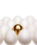 Configurações de um ovo do ouro entre ovos brancos comuns Imagens de Stock