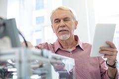 Configurações em mudança do homem superior da impressora 3D de acordo com a instrução foto de stock