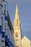 Configuración del sol de la última tarde en el chapitel y la aguja de la iglesia en última hora de la tarde fotos de archivo libres de regalías
