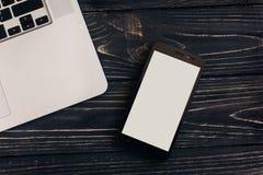 Configuration élégante d'appartement d'ordinateur portable et de téléphone avec l'écran vide sur le noir Photos stock