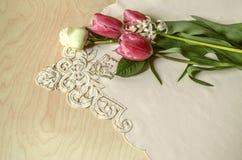 Configuration blanche de rose et de jacinthe de blanc de tulipes rouges sur la nappe brodée Photo stock