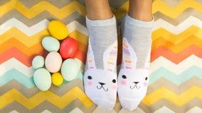 Configuration d'appartement d'amusement des chaussettes de port de lapin de personne avec des oeufs de pâques blA image libre de droits