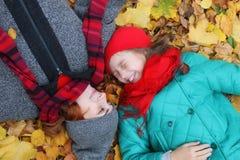 Configuration de fille et de mère l'automne de feuilles de la terre Image stock