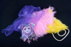 Configuration de masque de porcelaine sur des plumes couvertes par la fabrication violette près du collier de perle sur le fond n Photo stock
