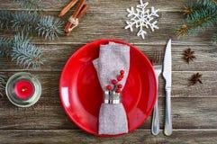 Configuration de table de Noël Plat rouge, serviette, fourchette, couteau, branche d'un arbre sur une table en bois photo libre de droits