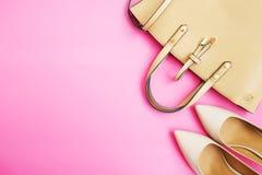 Configuration féminine d'appartement d'accessoires Chaussures et sac de femme sur le fond rose Accessoires beiges de femme de cou Images stock