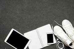 Configuration occasionnelle élégante d'appartement des espadrilles blanches sur le fond noir avec le téléphone, écouteurs, compri Photos libres de droits